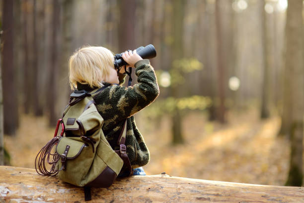 Little boy scout with binoculars during hiking in autumn forest. Child is sitting on large fallen tree and looking through a binoculars. stock photo