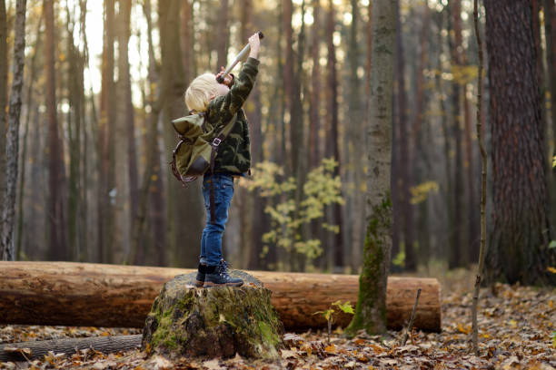 Little boy scout with spyglass during hiking in autumn forest. Child is looking through a spyglass. stock photo