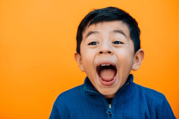 petit garçon crier d'excitation - sourire à pleines dents photos et images de collection