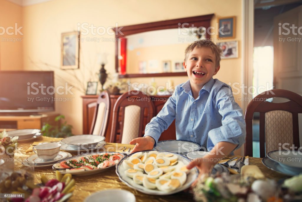 Little boy setting the table for traditional easter breakfast stock photo