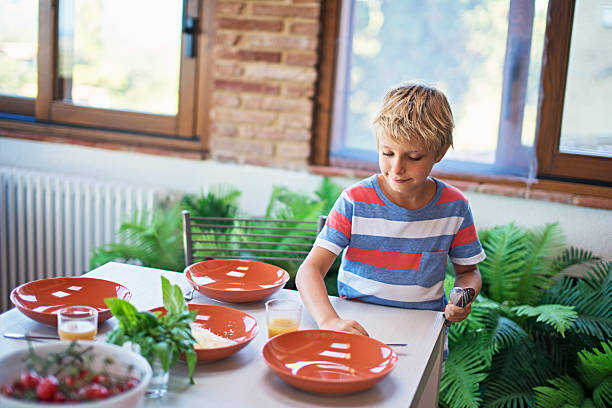 little boy setting up table for family lunch. - arranging stock photos and pictures