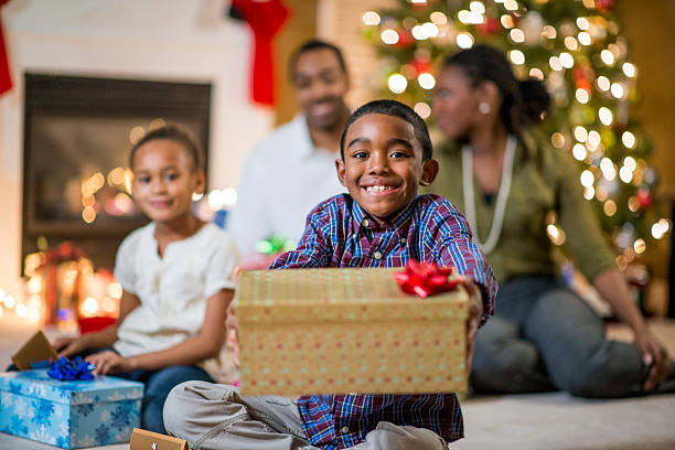 little boy sharing christmas gifts stock photo