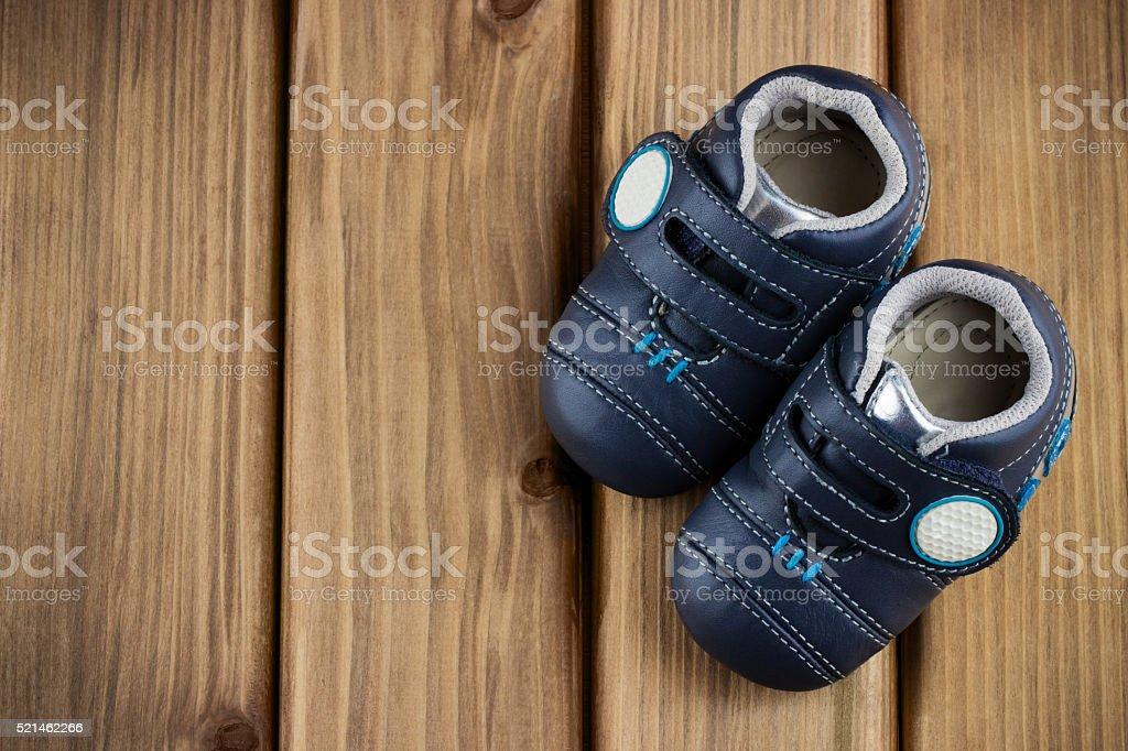 Schuhe für kleine Jungen in der Ecke auf einem hölzernen Hintergrund – Foto