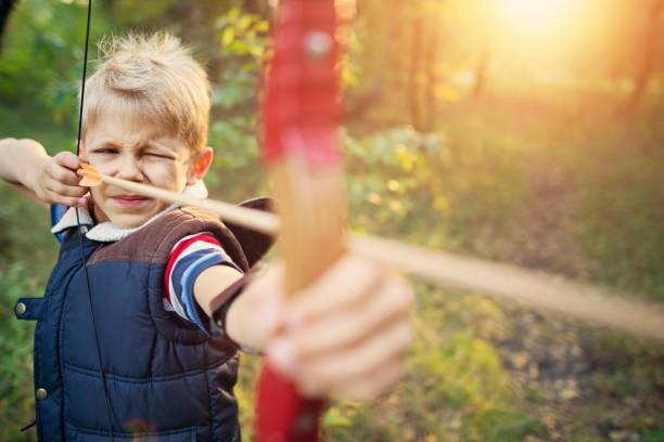petit garçon tir arc en forêt - tir à l'arc photos et images de collection