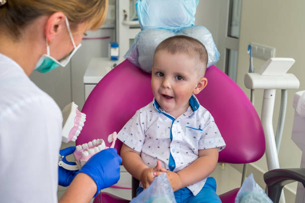Little boy showing his teeth to a doctor stock photo