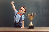 A cute, self-confident 2-3 years old boy is standing and showing his thumb up behind a wooden table with a golden trophy on it. Little boy is wearing an orange bow tie and blue trousers with suspenders.