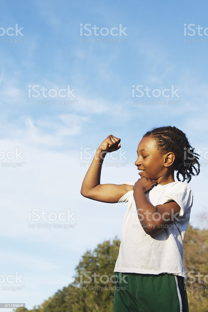 Little boy showing off his muscles on a bright day stock photo