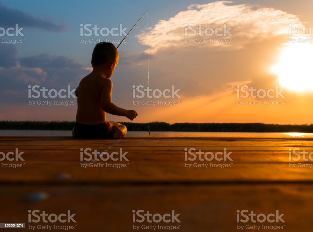 Little boy siting on wooden dock and fishing at sunset. stock photo