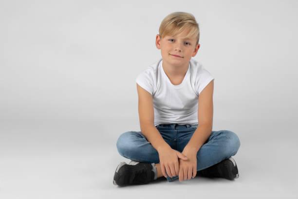 kleiner Junge sitzt im Schneidersitz auf dem Boden – Foto