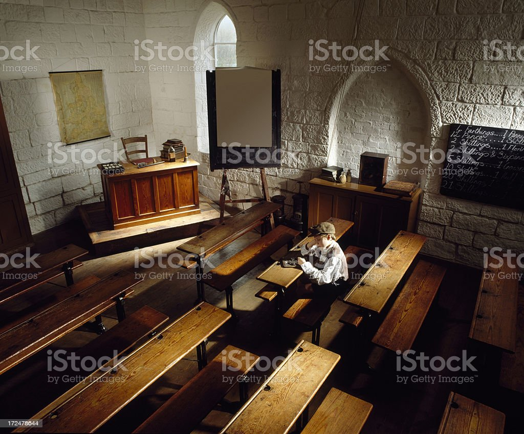 Little boy sitting alone in olden days class room stock photo