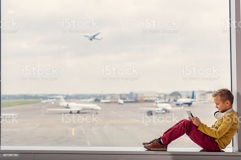 Little boy sitting at airport stock photo