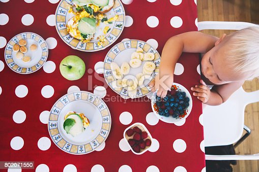 istock Little boy sitting at the table, eating breakfast. 802071550