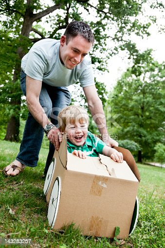 496487362 istock photo Little boy sitting in a cardboard car and being pushed 143283257