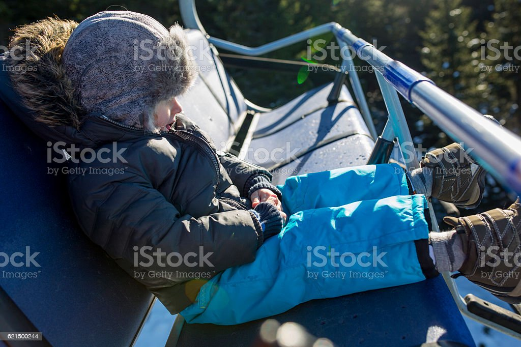 Little boy sitting in a ski lift during winter day. photo libre de droits