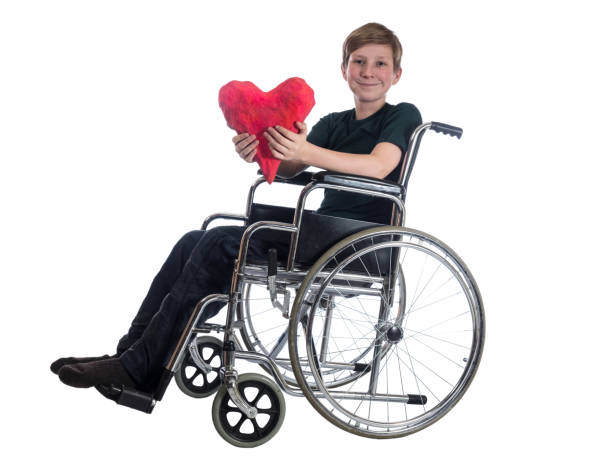 Little boy sitting in a wheelchair, smiling and holding in his hands a big red heart on a white background stock photo