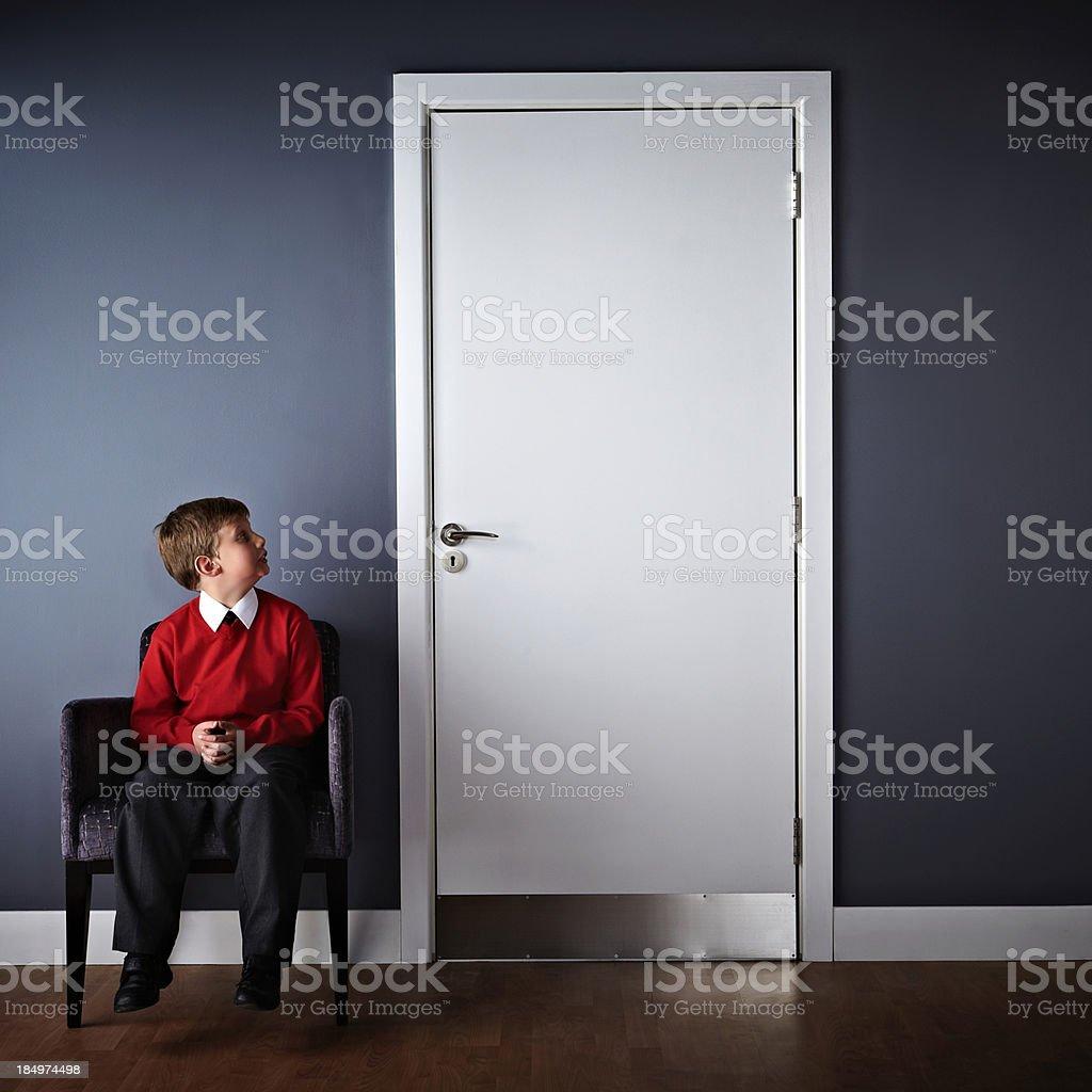 Little boy sitting in front of headmaster office stock photo