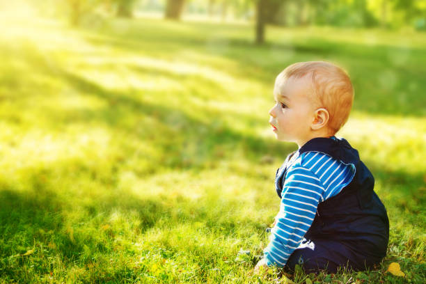 Little boy sitting in the park stock photo