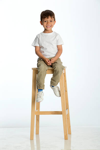 little boy sitting on a high stool - sitting stock pictures, royalty-free photos & images