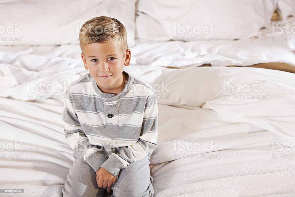 Little boy sitting on bed stock photo