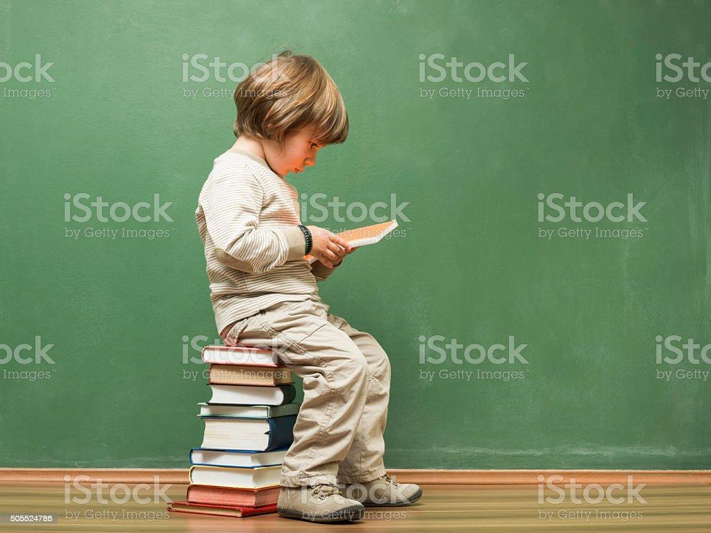 Little Boy Sitting On Books In Front Of Blackboard stock photo