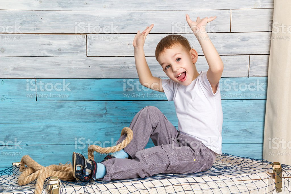 little boy sitting on box, lifting his hands up rejoices stock photo