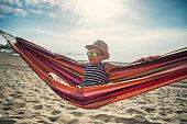 Little boy resting on beach hammock. The boy is wearing sunglasses and is taking selfie.