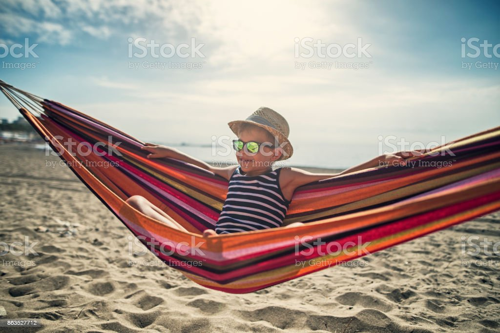 Little boy sitting on hammock on beach stock photo
