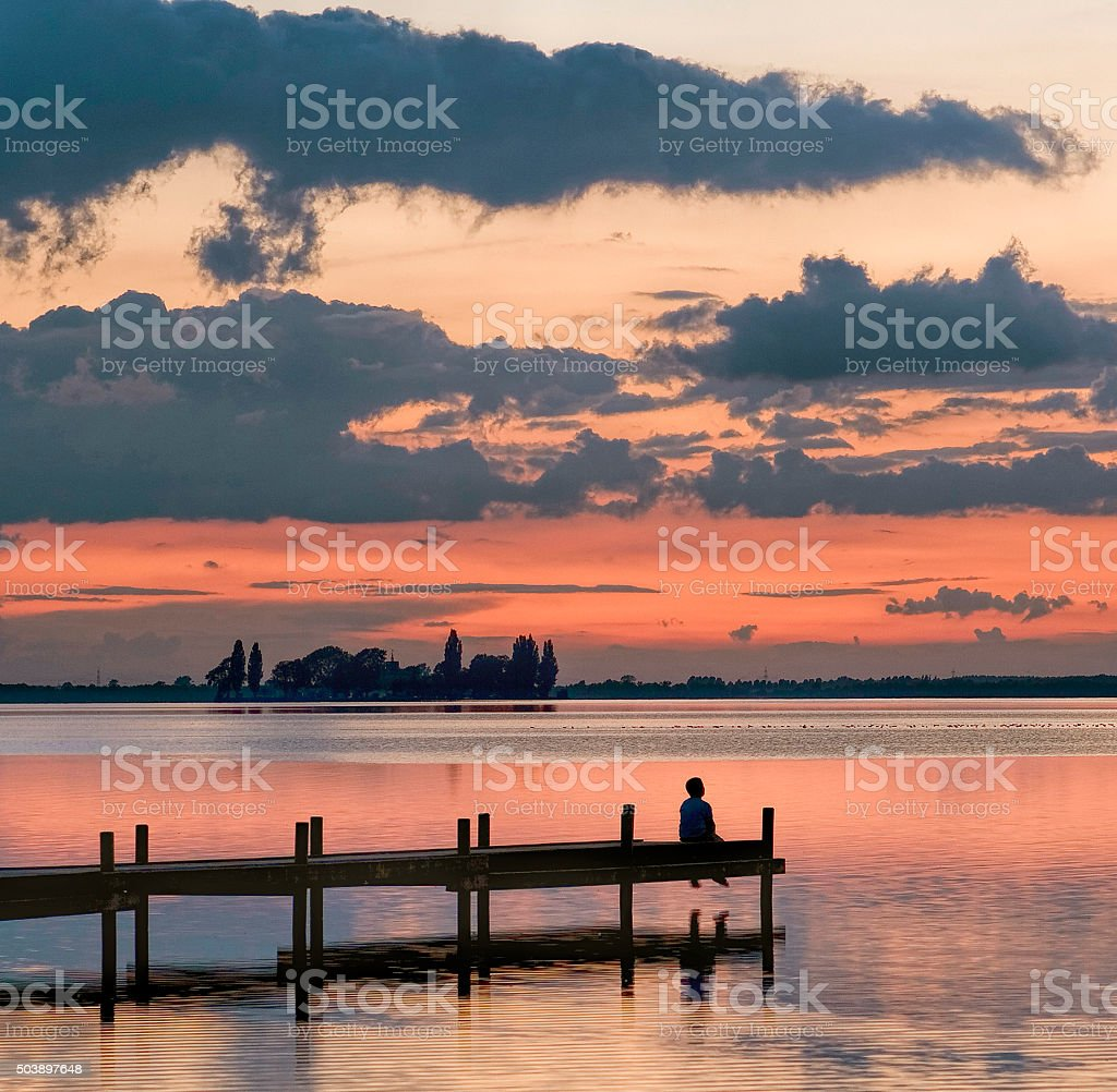 Little boy sitting on lakeside jetty with majestic cloudscape stock photo