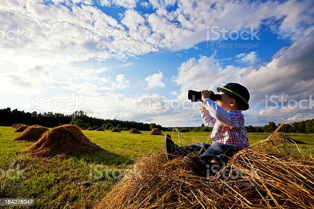 Photo of Little boy sitting on mounds of hay