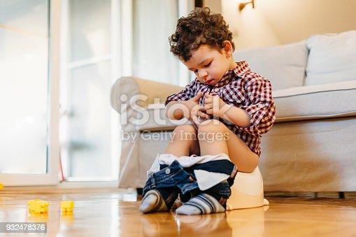 istock Little boy sitting on potty 932478376