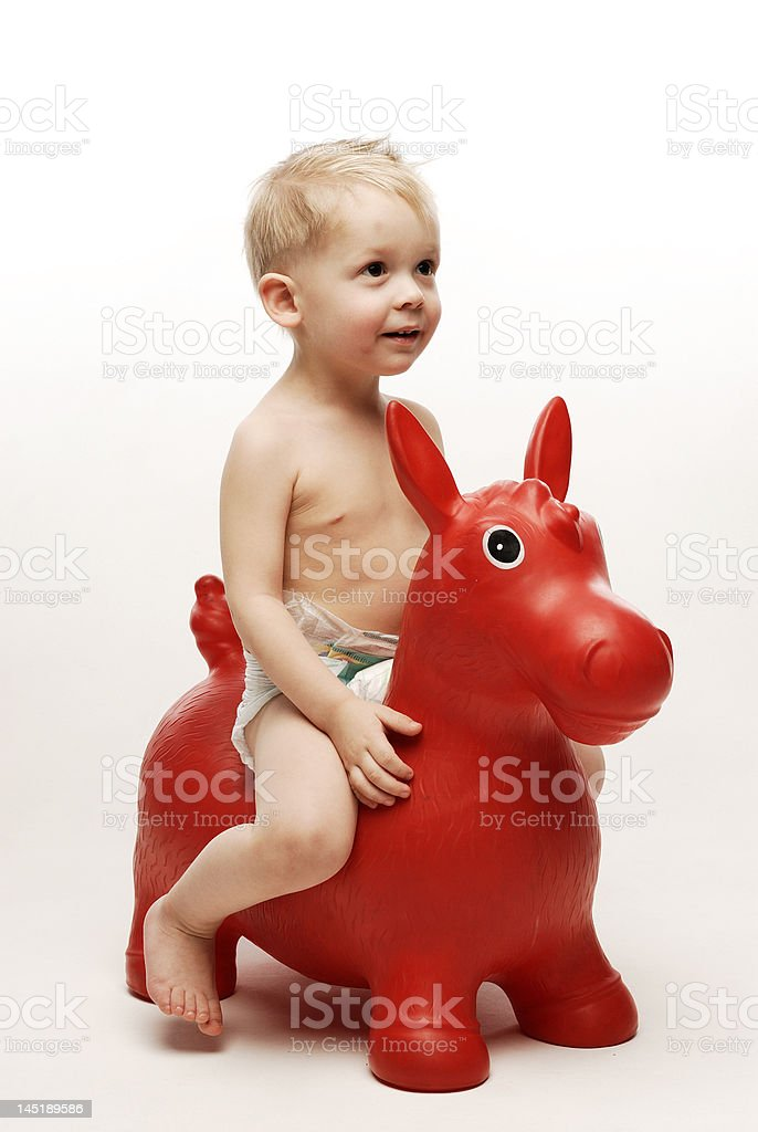 Little boy sitting on red horse looking up royalty-free stock photo