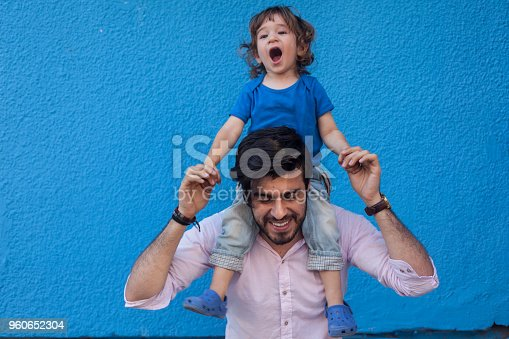 Little boy sitting on shoulders of adult man in front of blue wall. Adult man has facial hair. Shot in outdoor daylight with a full frame DSLR camera.