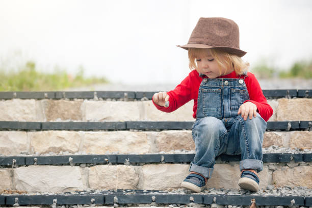 Little boy sitting on stairs Little blonde boy sitting on stairs and playing with pebbles bib overalls boy stock pictures, royalty-free photos & images