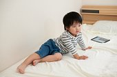 Little boy sitting on the bed with his tablet