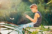 Boy watching a dragonfly which he caught.