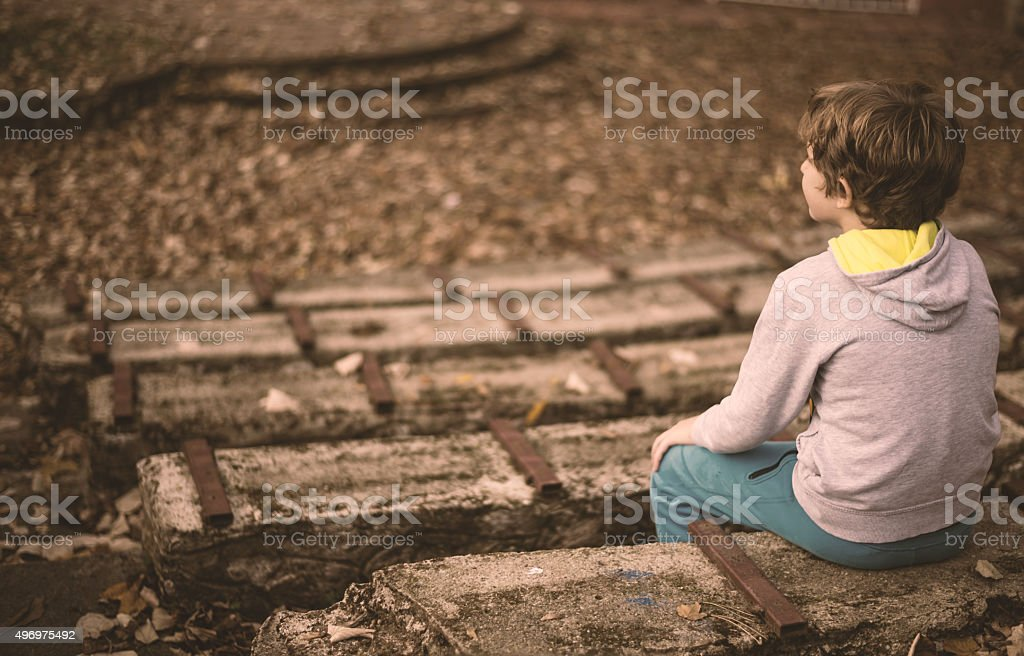 Little boy sitting on the stairs stock photo
