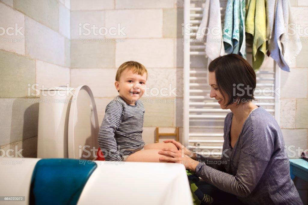 Kleiner Junge schöne Mutter hielt ihn auf der Toilette sitzend – Foto