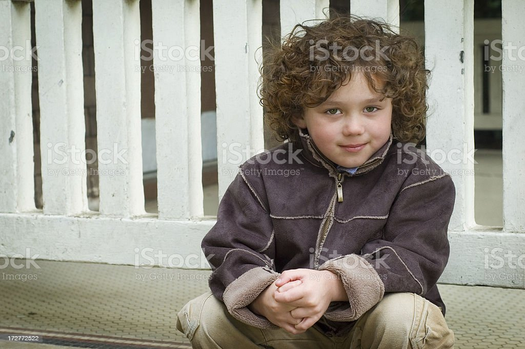 Little Boy Sitting on wall background royalty-free stock photo