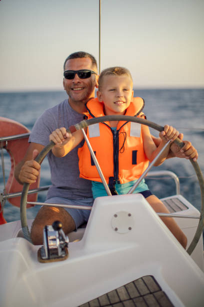 Little boy sitting with father and steering with sailboat stock photo