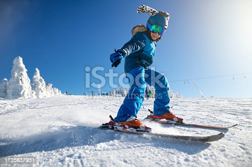 Little boy skiing on a beautiful sunny winter day.  The boy is speeding on a modern wide ski slope. Nikon D850