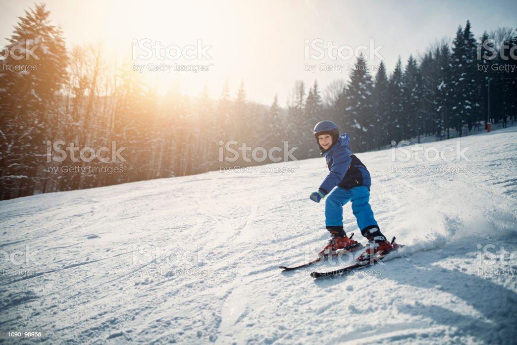 Kleiner Junge Skifahren an einem sonnigen Wintertag – Foto