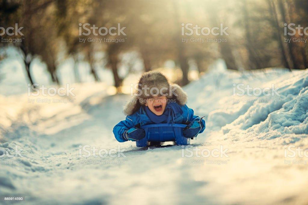 Little boy sledding and shouting stock photo