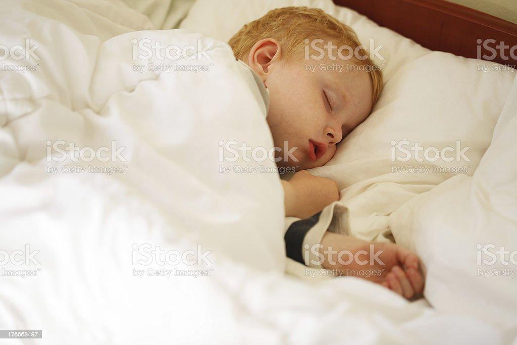 Poco niño durmiendo en la cama foto de stock libre de derechos