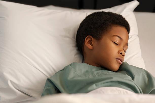 little boy sleeping in the hospital stock photo