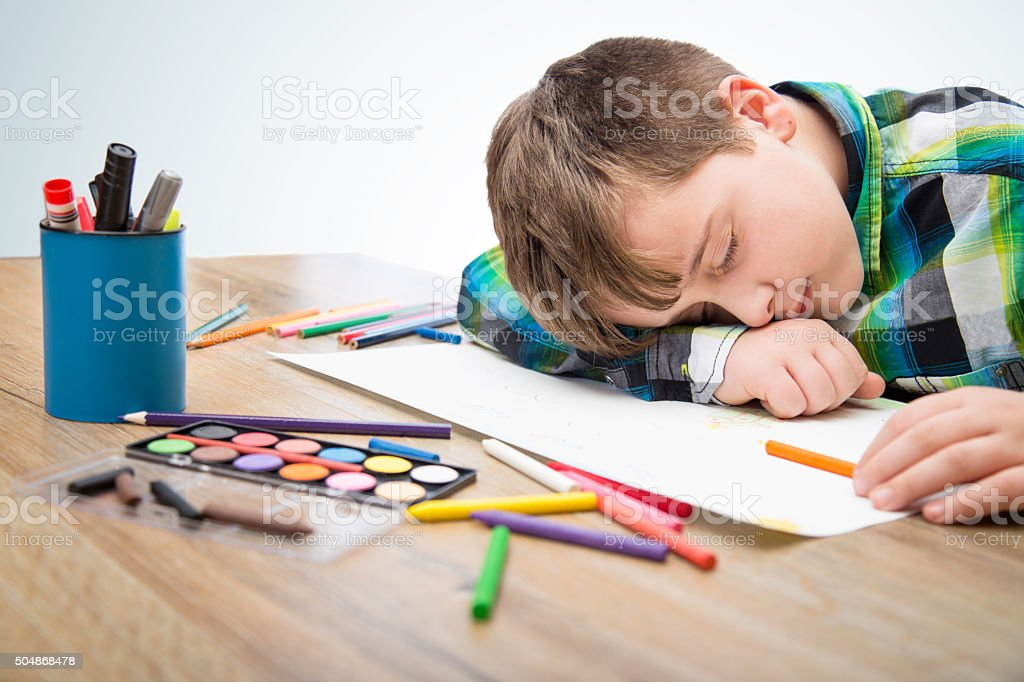 Little Boy Sleeping On Blank Paper With Crayons Royalty Free Stock Photo