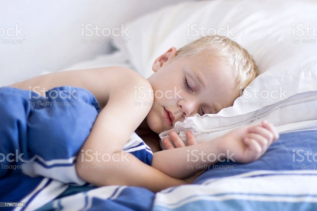 A little boy sleeping on his side in a blue bed stock photo