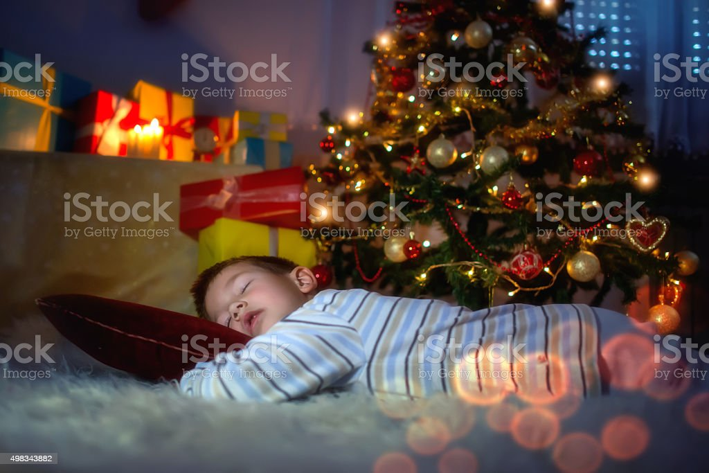 Little boy sleeping under the Christmas tree stock photo