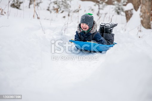 Little Boy Sliding in the Snow Outdoors in Winter. He is smiling and having a lot of fun.