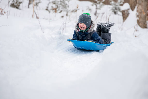 Little Boy Sliding in the Snow Outdoors in Winter stock photo