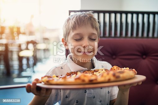 Little boy aged 8 smelling just cooked pizza in restaurant. Nikon D850